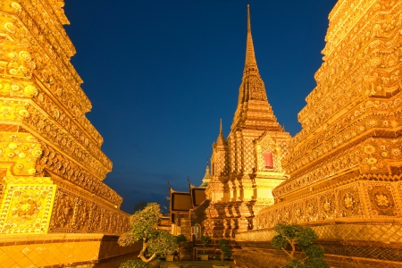 maha: Wat Pho is a first grade royal monastery, located in the old town of Bangkok  This picture shows the Phra Maha Chedi Si Ratchakan, a group of four large  42m  chedis covered with flower mosaics, illuminated to create a golden glow which is visible from fa Stock Photo