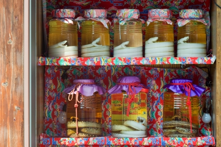 shop for animals: Habu snakes which are found only on Okinawa are put into jars of awamori, a liquor local to the island which is like sake but stronger The jars are sold from the colourful shelves of a shop in Naha, Okinawa, Japan