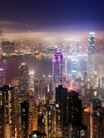 An aerial view over the Hong Kong skyline at night time, the haze adds a mystic touch to the scenery photo