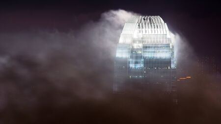 The  International Finance Centre in Hong Kong emerging from clouds, shot at nighttime  Stock Photo - 15461736