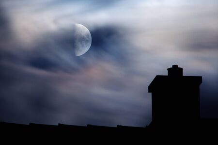 A half moon behind dreamy clouds above a rooftop silhouette  Stock Photo - 15793741