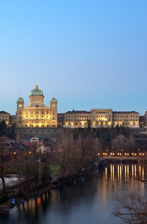 swiss culture: The Swiss parliament building  Bundeshaus  in Bern under a deep blue evening sky in winter  Below is the river aar  Aare