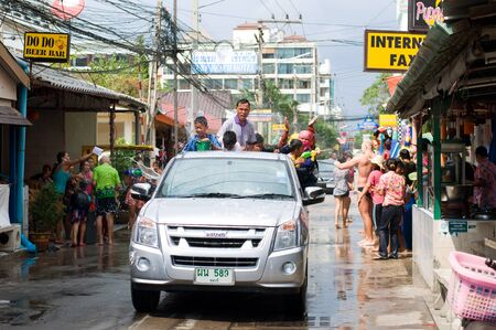 revellers: Pattaya, Chon Buri, Thailand - April 14, 2011: Street scene during Songkran festival at Jomtien Beach in Pattaya: A pick-up loaded with thai songkran revellers is cruising trough a soi. Songkran is the annual traditional Thai new year festival.  It is cel