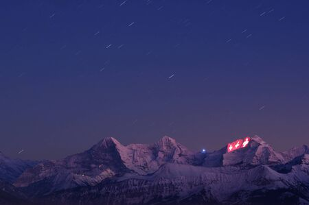 swiss insignia: Thun, Switzerland - January 12, 2012: Three Swiss crosses being projected on the face of the Jungfrau as a part of the 100 year festivities of the Jungfrau railway.