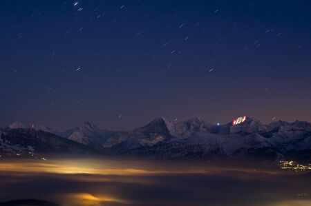 switzerland flag: Thun, Switzerland - January 12, 2012: Swiss crosses being projected on the face of the Jungfrau as a part of the 100 year festivities of the Jungfrau railway.