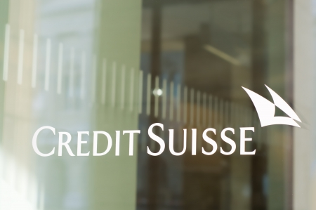 cs: Bern, Switzerland - February 18, 2012: The Credit Suisse logo in a window of a branch. CS is a globally active financial services company offering investment banking, asset and wealth management.