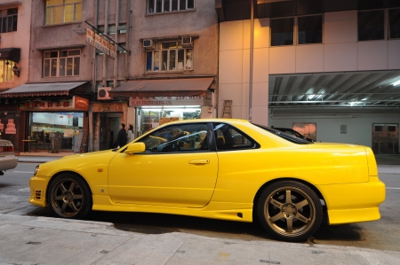 nissan: Fortress Hill, Hong Kong - March 25, 2011: A yellow tuned Nissan Skyline R34 GT-R parked in the streets of Hong Kong