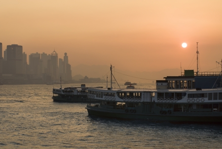 Star ferry passenger boats at sunset in Victoria Harbour,  Hong Kong  photo