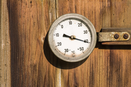 weather gauge: A vintage thermometer  mounted on a wooden wall in direct sunlight.