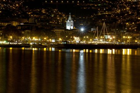 Night photo of a city by the sea in Funchal, Madeira.