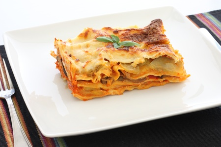lasagna: Vegetarian lasagna with eggplant, courgette, sweet potatos and tomato sauce on a white plate. Stock Photo