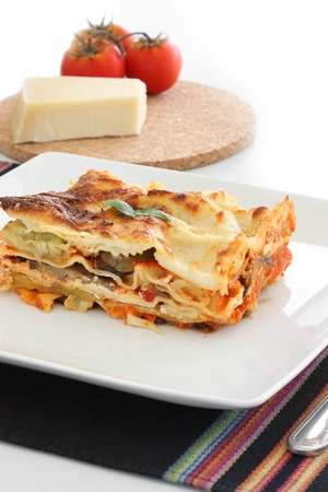Vegetarian lasagna with eggplant, courgette, sweet potatos and tomato sauce on a white plate. Stock Photo
