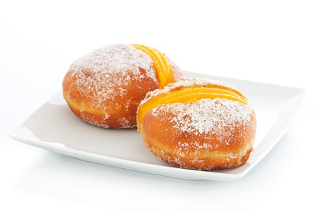 Portuguese doughnut or Berliner with egg creme over a white plate Stock Photo