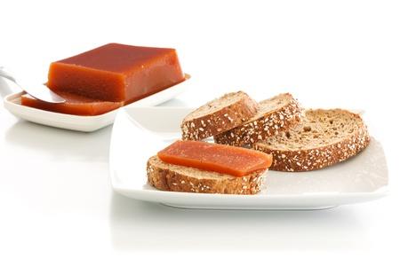 membrillo: Quince rebanadas de mermelada en el pan semillas en un plato sobre un fondo blanco