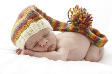 sleep: Bebé recién nacido durmiente que lleva un sombrero multicolor de largo. Foto de archivo