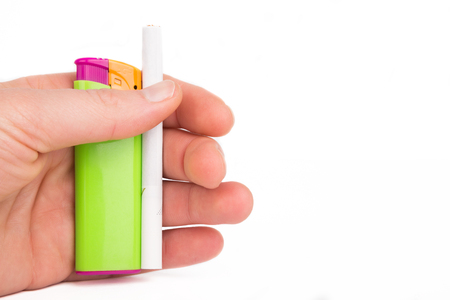 Hand holding a coloured plastic lighter and a cigarette isolated on white. photo