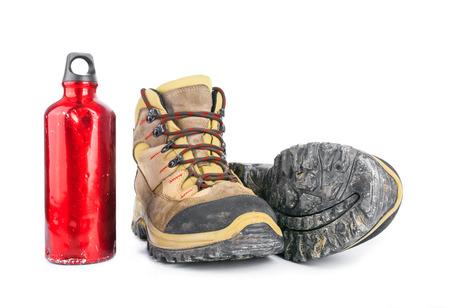 botas: Botas sucias usados ??y botella de agua de color rojo maltrecho viejo aislado en el fondo blanco.