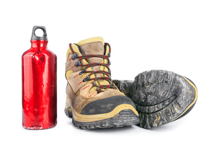 muddy clothes: Used Dirty hiking boots and old battered red water bottle isolated on white background. Stock Photo