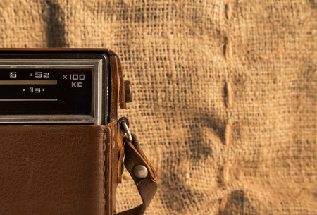 transistor: Part of an old transistor radio in a leather case on a background of a burlap.