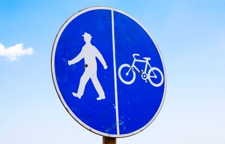 segregated: Bicycle and pedestrian lane sign against the blue sky.
