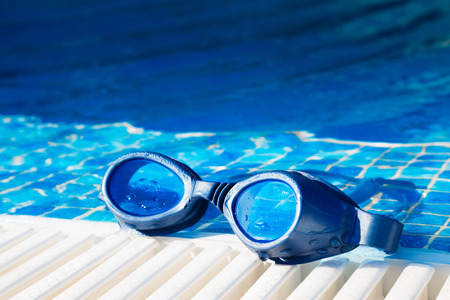 poolside: Image of a swimming pool goggles on the poolside.