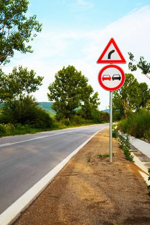overtake: No overtake and three-cornered right turn sign on a highway in Europe. Stock Photo