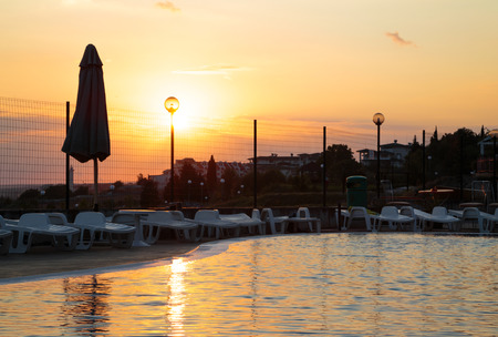 umbrela: Sunset over a swiming pool in a summer hotel at the seaside.