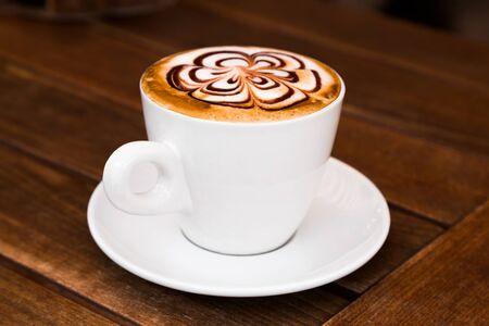 capuchino: Taza de capuchino de café en una mesa de madera. Arte Cappuccino.
