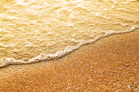 gleams: Closeup image of beautiful ripple on a beach at sunrise. Blank area for text in the foreground. Stock Photo