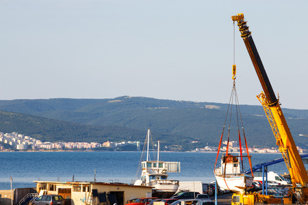 starboard: Moving of boat with crane in a port