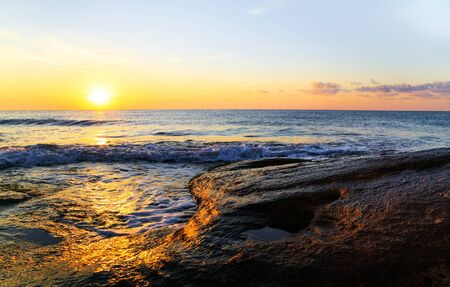 swells: Tropical ocean sunrise with the fiery orb of the sun hanging low over the horizon in a colorful orange sky above a calm ocean with swells. Stock Photo