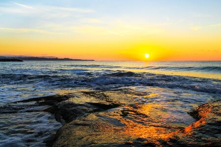 swells: Sunrise over the sea, Black sea coast, Bulgaria. Sunrise with the fiery orb of the sun hanging low over the horizon in a colorful sky above a calm sea with swells.