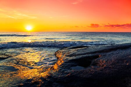 sunny beach: Tropical ocean sunrise with the fiery orb of the sun hanging low over the horizon in a colorful orange sky above a calm ocean with swells. Stock Photo