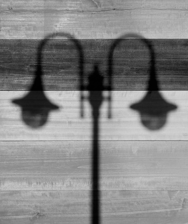architectural lighting design: Close up Shadow of Street Lamps with Two Light Bulbs on a  Wooden Background with Horizontal Pattern. Black and White image.