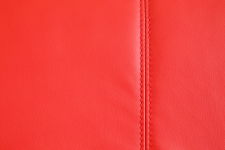 Background full frame texture of Red artificial leather with a stitched seam on an upholstered settee or couch in an interior decorating concept. Stock Photo