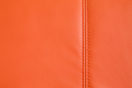 Background full frame texture of Orange artificial leather with a stitched seam on an upholstered settee or couch in an interior decorating concept. Stock Photo