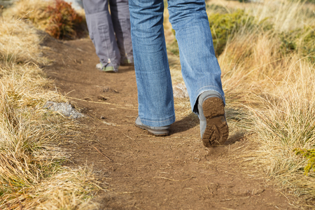 adventurers: Hikers walking along a sandy mountain footpath away from the camera, low angle view of the legs in a conceptual image