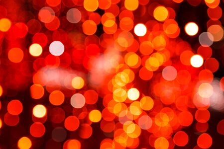 glitzy: Colorful festive bokeh background of a defocused blurred city lights in shades of red and orange in a full frame view. Stock Photo