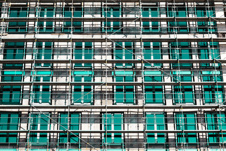 low angle view: Low angle view of rows and columns of metal scaffolding over rectangular windows on building outdoors.