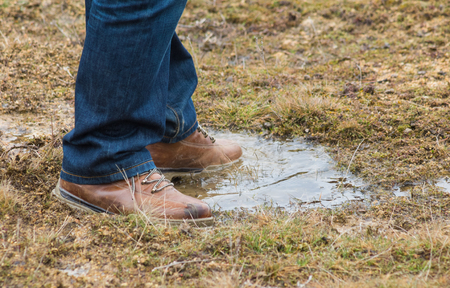 lace up: Feet of a person wearing lace up shoes and blue denim jeans standing in a puddle of water in short scrubby grass.
