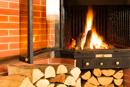 close up chimney: Hot wood fire burning in a chimney insert for heating a home or house in winter using natural renewable resources for fuel with stacked wood below on a brick wall.