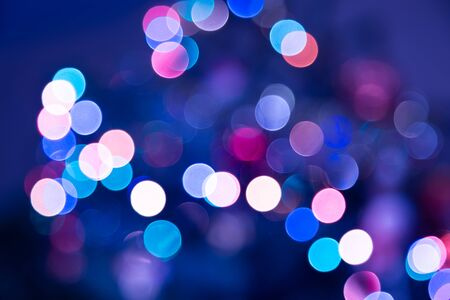 Blue colored festive bokeh background of a defocused blurred city lights in shades of pink and purple in a full frame view.