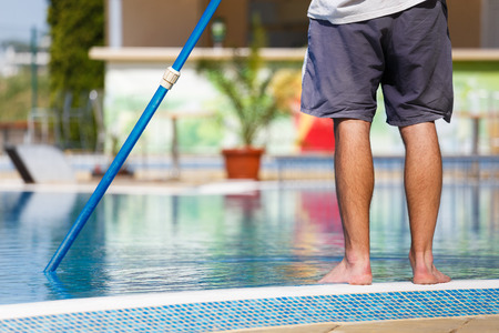 Man cleaning a swimming pool in summer with a brush or net on a blue pole standing barefoot