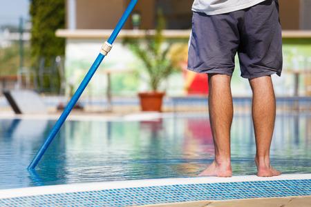 mantenimiento: Hombre de limpieza de una piscina en verano con un cepillo o una red en un poste azul de pie descalzo