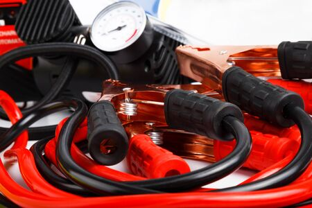coiled: Close up low angle on a coiled set of red and black starter cables or jump leads and a pressure gauge for a car.
