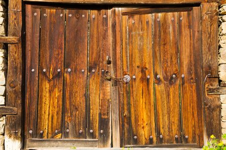 Old double rustic wooden barn doors in stone walls made from rows of nails and timber planks locked with a chain.
