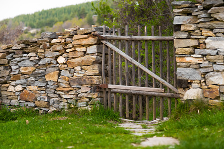 entrance gate: Rustic handmade wooden gate made from natural wooden poles in a stone wall with a path leading to a rural hillside.