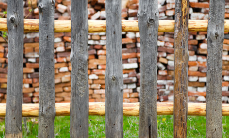 lawn area: Rustic wooden fence with a cabin or rural cottage wall visible beyond and a green lawn area.