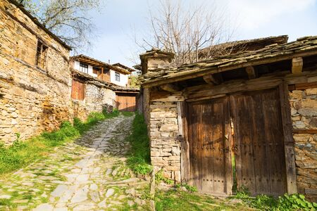 real renaissance: Village of Leshten, Bulgaria. Entrance driveway to a rustic stone house with old outbuildings with weathered wooden doors and the house in the background.