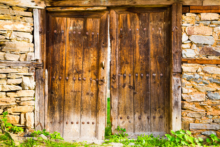 weatherworn: Old double rustic wooden barn doors in stone walls made from rows of nails and timber planks